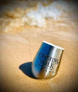 Captain's Walk Tumbler in the sand. Waves in the background